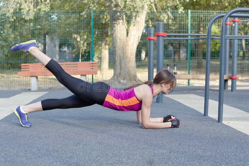 Νέα καυκάσια γυναίκα workouts στο πάρκο sportsground Λεπτό κορίτσι στη θέση σανίδων, ένα πόδι επάνω, φωτεινό sportswear Ακουστικά στοκ φωτογραφία