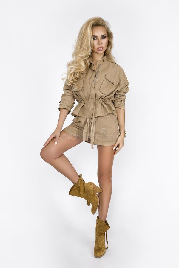 Νέα μόδα, μοντέρνη χαμογελώντας ξανθή γυναίκα στο στούντιο Ενδυμασία τάσης μόδας, ύφος σαφάρι, θερινή εξάρτηση, άσπρο υπόβαθρο, στοκ εικόνα με δικαίωμα ελεύθερης χρήσης