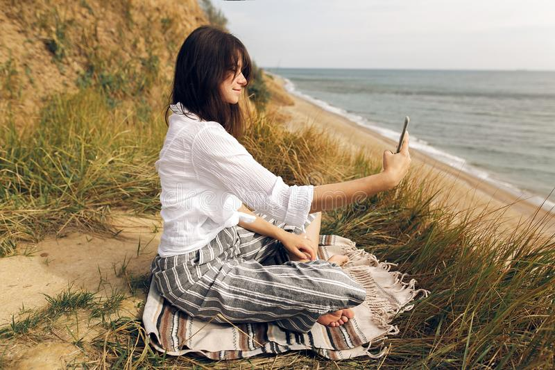 Νέα όμορφη γιόγκα άσκησης γυναικών στην παραλία, κάθισμα στη χλόη και εξέταση το τηλέφωνο, που παίρνει selfie Κορίτσι Hipster που στοκ εικόνα με δικαίωμα ελεύθερης χρήσης