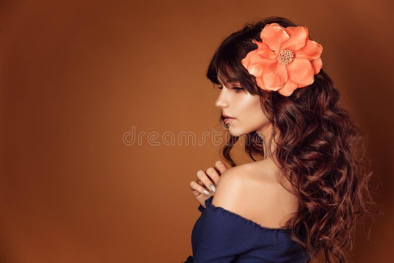 Νέα όμορφη γυναίκα με τα λουλούδια στην τρίχα της και makeup, τονίζοντας φωτογραφία στοκ φωτογραφίες με δικαίωμα ελεύθερης χρήσης