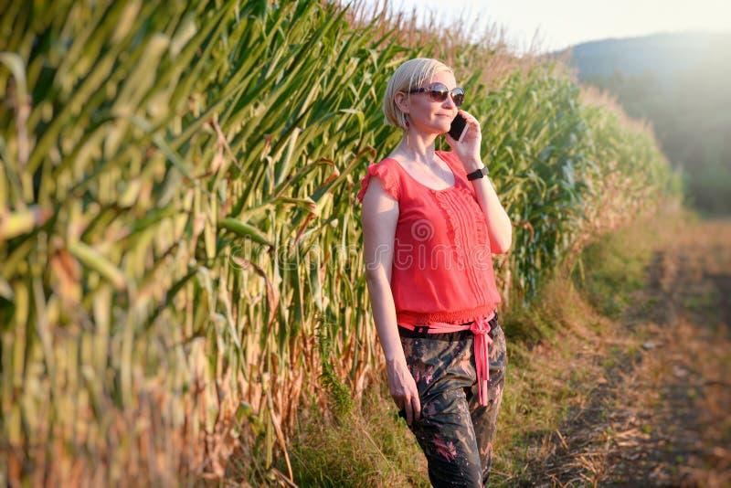 Νέα όμορφη γυναίκα στη ζωηρόχρωμη υπαίθρια ομιλία υφασμάτων και γυαλιών ηλίου στο τηλέφωνο κυττάρων στοκ εικόνες με δικαίωμα ελεύθερης χρήσης