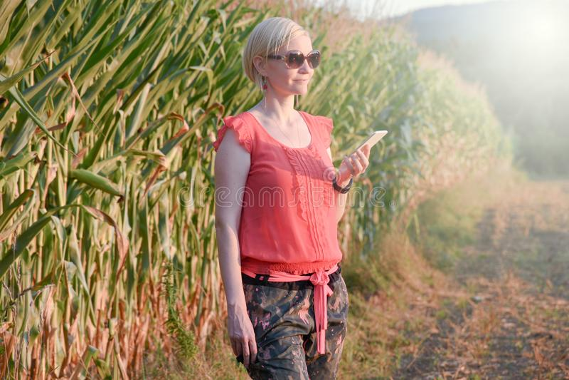 Νέα όμορφη γυναίκα στη ζωηρόχρωμη υπαίθρια ομιλία υφασμάτων και γυαλιών ηλίου στο τηλέφωνο κυττάρων στοκ εικόνες