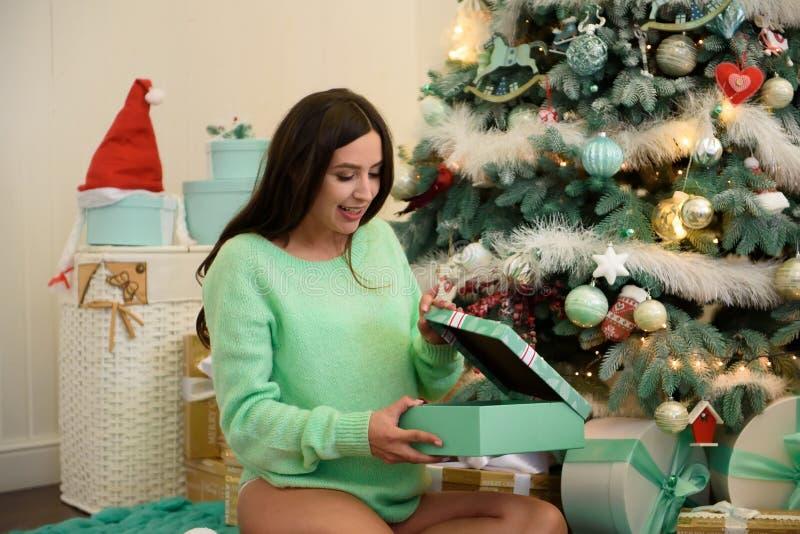 Νέα όμορφη ευτυχής έγκυος γυναίκα που εγκαθιστά κοντά στο νέο δέντρο έτους και που ανοίγει ένα δώρο στοκ εικόνες
