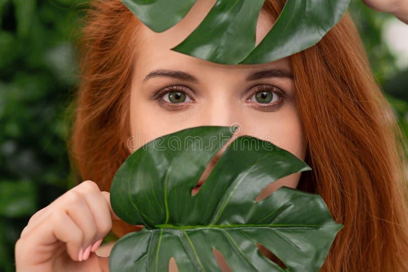 Νέα redhead γυναίκα με το φυσικό makeup στα πράσινα φύλλα monstera στοκ εικόνα