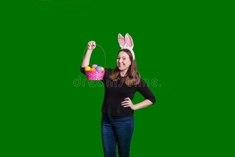 Νέες γυναίκες που κρατούν ψηλά το ρόδινο καλάθι αυγών Πάσχας που φορά τα αυτιά λαγουδάκι στοκ φωτογραφία