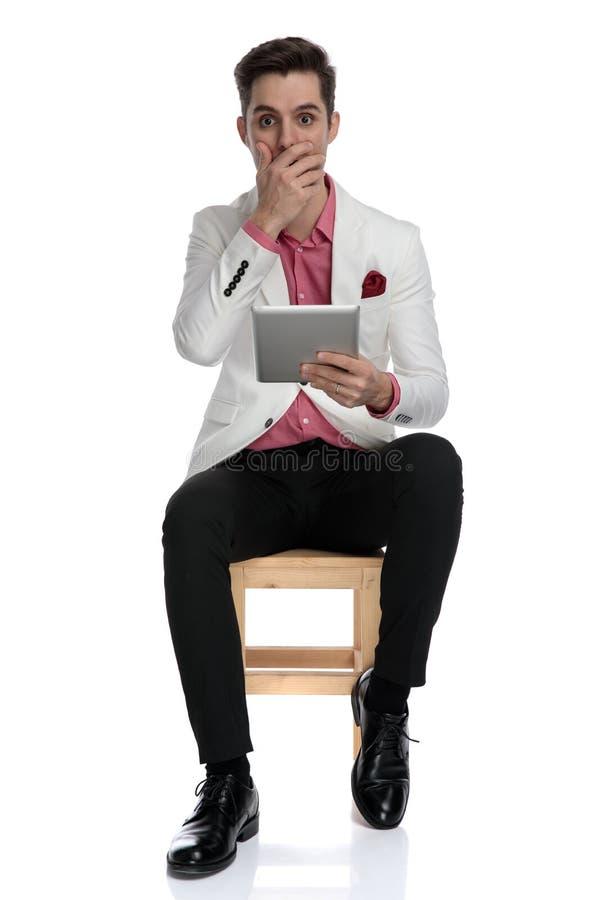 Νέες καθισμένες καταπληκτικές ειδήσεις ανάγνωσης επιχειρηματιών στην ταμπλέτα του στοκ εικόνα