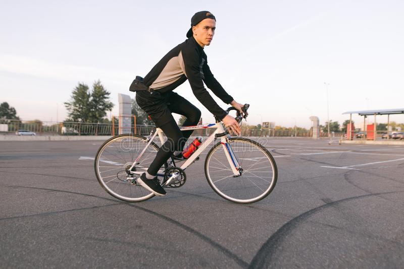 Νέοι γύροι ποδηλατών σε έναν χώρο στάθμευσης αυτοκινήτων για ένα ποδήλατο στοκ εικόνες με δικαίωμα ελεύθερης χρήσης