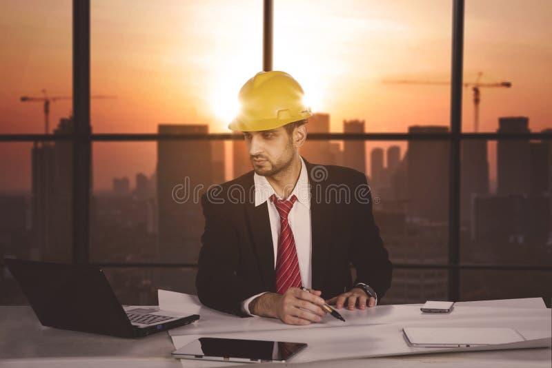 Νέος αρσενικός αρχιτέκτονας που εργάζεται στο γραφείο στοκ εικόνα
