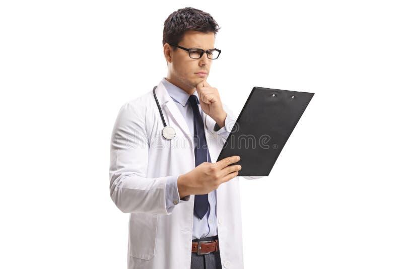 Νέος αρσενικός γιατρός που εξετάζει ένα έγγραφο για μια περιοχή αποκομμάτων και μια σκέψη στοκ φωτογραφίες με δικαίωμα ελεύθερης χρήσης