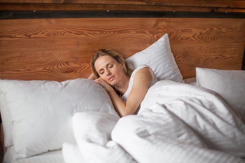 Νέος ύπνος γυναικών στο κρεβάτι το πρωί, που αγκαλιάζει το μαξιλάρι της, διάστημα αντιγράφων στοκ εικόνα