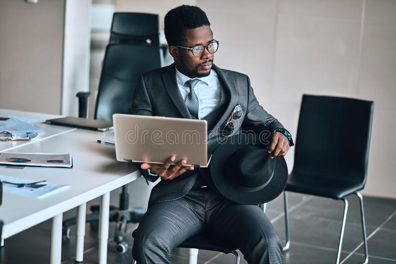 Νέος σκεπτικός κομψός επιχειρηματίας αφροαμερικάνων που χρησιμοποιεί το lap-top στοκ εικόνες