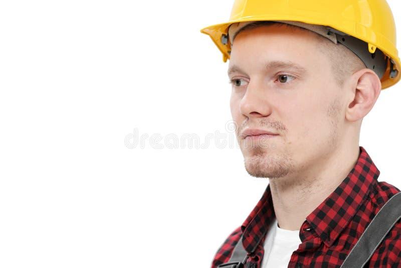 Νέος χαμογελώντας άνδρας εργαζόμενος σε έναν εργάτη οικοδομών, σε ένα κίτρινο κράνος, τις λειτουργώντας φόρμες και ένα κόκκινο ελ στοκ φωτογραφία με δικαίωμα ελεύθερης χρήσης