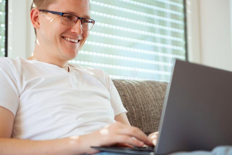 Νέο αρσενικό freelancer που εργάζεται με το lap-top στο σπίτι στοκ φωτογραφίες
