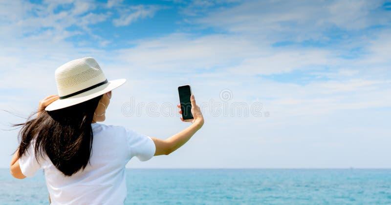 Νέο ασιατικό καπέλο ένδυσης γυναικών στο περιστασιακό smartphone χρήσης ύφους που παίρνει selfie στην αποβάθρα Θερινές διακοπές σ στοκ εικόνα