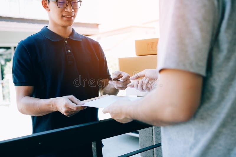 Νέο ασιατικό προσωπικό παράδοσης που κρατούν τη μάνδρα και τα έγγραφα υποβάλλοντας το δόσιμο στον πελάτη που λαμβάνει το δέμα στο στοκ εικόνα με δικαίωμα ελεύθερης χρήσης