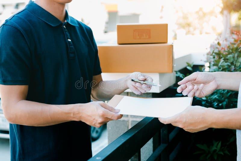 Νέο ασιατικό προσωπικό παράδοσης που κρατούν τη μάνδρα και τα έγγραφα υποβάλλοντας το δόσιμο στον πελάτη που λαμβάνει το δέμα στο στοκ εικόνες