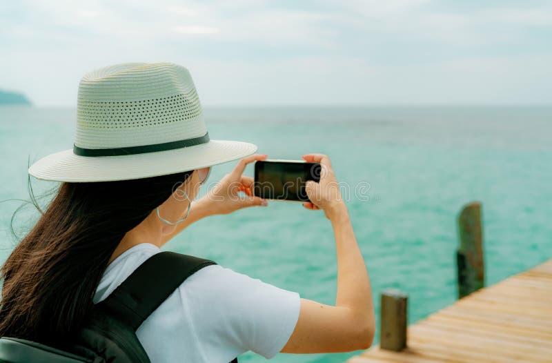 Νέο ασιατικό smartphone χρήσης καπέλων ένδυσης γυναικών backpacker που παίρνει τη φωτογραφία στην αποβάθρα Θερινές διακοπές στην  στοκ φωτογραφία με δικαίωμα ελεύθερης χρήσης