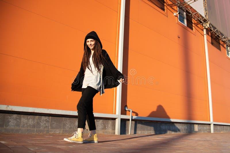 Νέο εύθυμο κορίτσι με μια κουκούλα και ένας μαύρος μανδύας στα πλαίσια ενός πορτοκαλιού τοίχου στοκ εικόνες