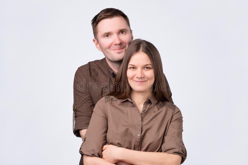 Νέο ζεύγος που στέκεται στο άσπρο υπόβαθρο, που αγκαλιάζει το χαμόγελο στη κάμερα στοκ φωτογραφίες με δικαίωμα ελεύθερης χρήσης