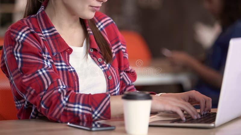 Νέο θηλυκό freelancer που επικοινωνεί με τον πελάτη στο lap-top, ρουτίνα εργασίας στοκ εικόνες