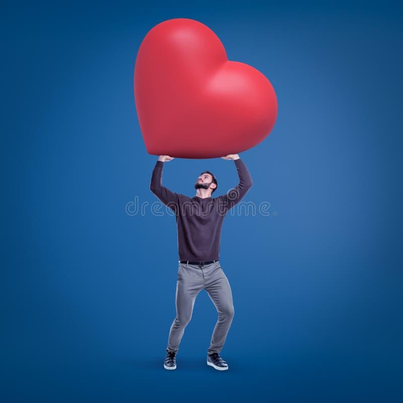 Νέο κατάλληλο άτομο στα περιστασιακά ενδύματα που κρατούν ψηλά την τεράστια κόκκινη καρδιά βαλεντίνων στο μπλε υπόβαθρο στοκ φωτογραφία