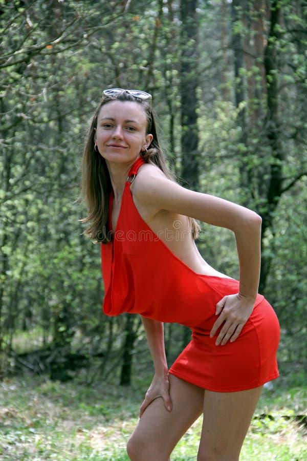 Νέο κορίτσι στο κόκκινο φόρεμα στο δάσος την άνοιξη στοκ φωτογραφία με δικαίωμα ελεύθερης χρήσης