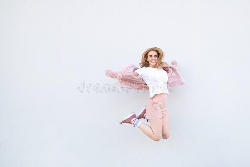 Νέο ξανθό κορίτσι στα ρόδινα ενδύματα που πηδά στα πλαίσια ενός άσπρων τοίχου και ενός χαμόγελου στοκ εικόνα