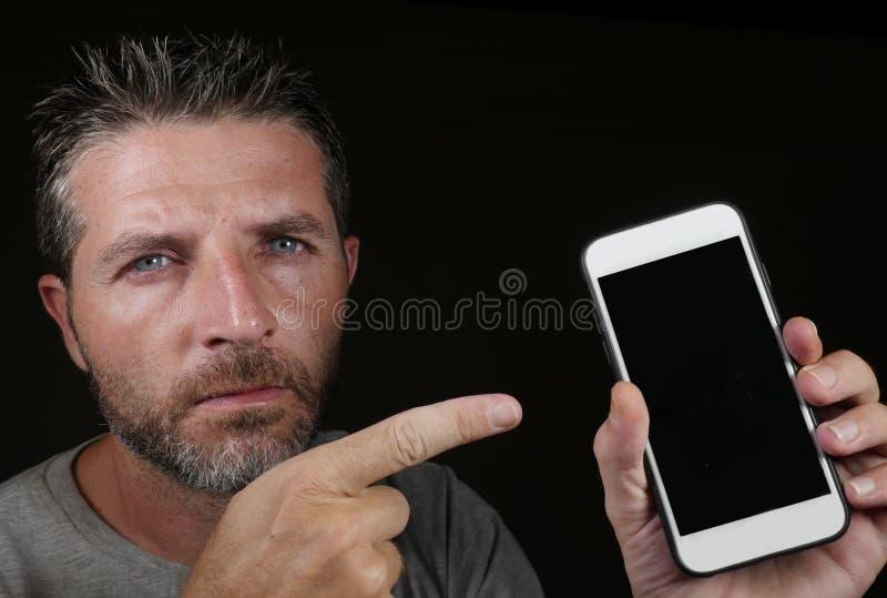 Νέο όμορφο και ελκυστικό καυκάσιο άτομο που κρατά το κινητό τηλέφωνο στο χέρι του που δείχνει το με το δάχτυλο που απομονώνεται σ στοκ εικόνες