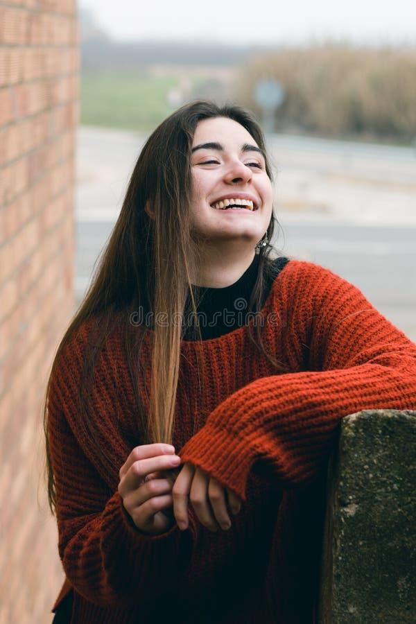 Νέο όμορφο και ευτυχές κορίτσι που χαμογελά και σχετικά με την τρίχα της σε μια αγροτική σκηνή Υπαίθρια πορτρέτο μόδας στοκ φωτογραφία