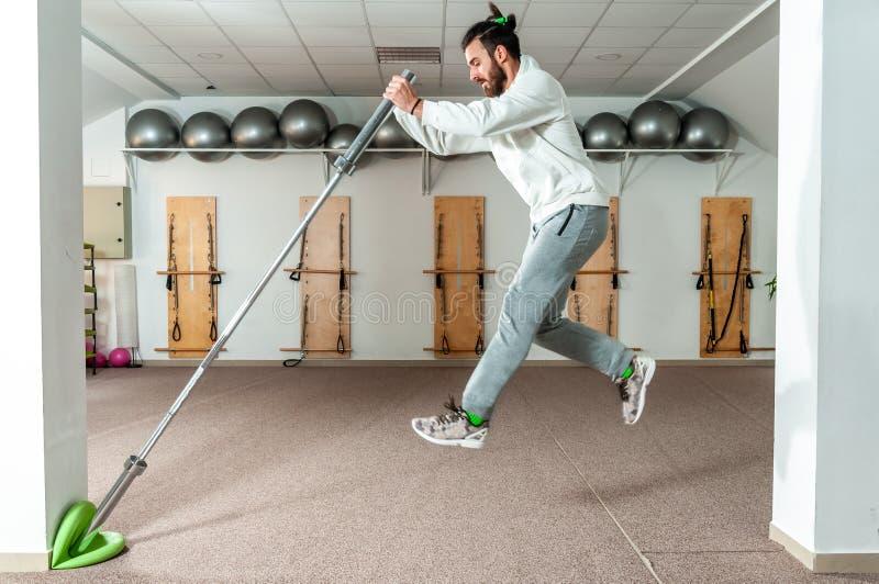 Νέο υγιές άλμα ατόμων ικανότητας με το φραγμό βάρους barbell ως άσκηση για την αντοχή και τη δύναμη στοκ εικόνα