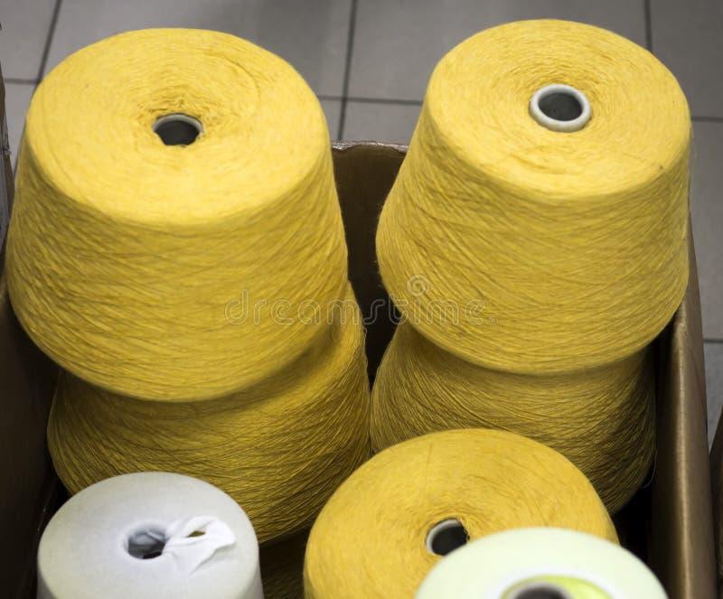Νήμα στα μουστάρδα-χρωματισμένα μασούρια σε ένα κιβώτιο στο εργοστάσιο στοκ εικόνα