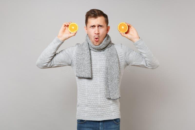 Ναρκωμένος νεαρός άνδρας στο γκρίζο πουλόβερ, πορτοκάλια εκμετάλλευσης μαντίλι στο γκρίζο υπόβαθρο τοίχων, πορτρέτο στούντιο Υγιή στοκ φωτογραφίες με δικαίωμα ελεύθερης χρήσης