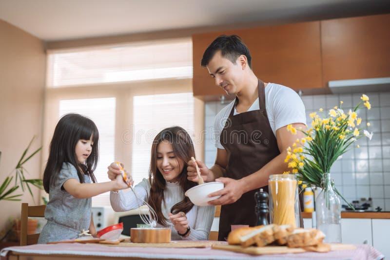 Να προετοιμαστεί γονέων βοήθειας κορών ψήνει την οικογενειακή έννοια στοκ φωτογραφίες