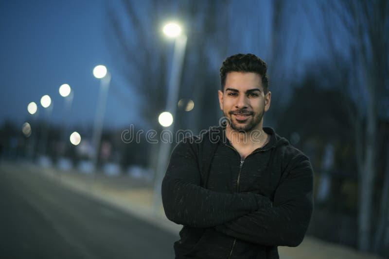 Νεαρός άνδρας με τα αθλητικά ενδύματα που θέτουν και που χαμογελούν στοκ φωτογραφία