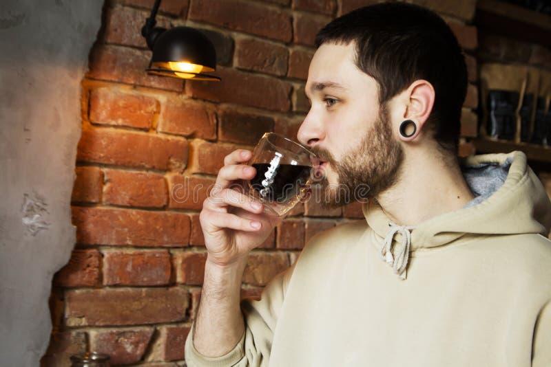 Νεαρός άνδρας που έχει το σπάσιμο με το φλιτζάνι του καφέ στοκ φωτογραφία