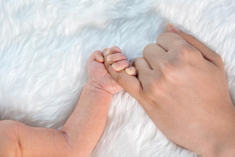 Νεογέννητο αγοράκι που κρατά λίγο δάχτυλο του χεριού της μητέρας στοκ εικόνες