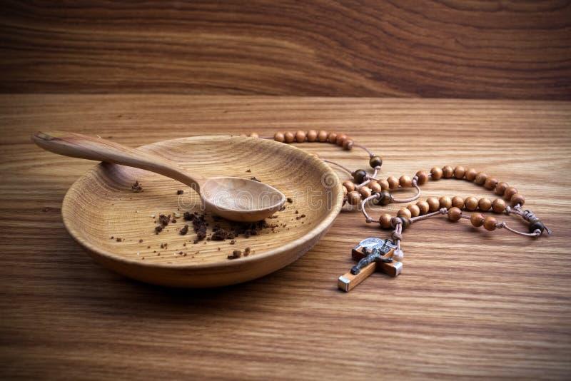 Νηστεία, που παραχωρεί Πιάτο και σταυρός στο ξύλινο backgroud στοκ φωτογραφία
