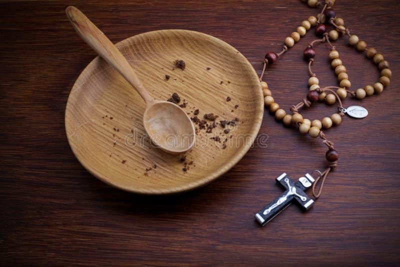 Νηστεία, που παραχωρεί Πιάτο και σταυρός στο ξύλινο backgroud στοκ φωτογραφία με δικαίωμα ελεύθερης χρήσης