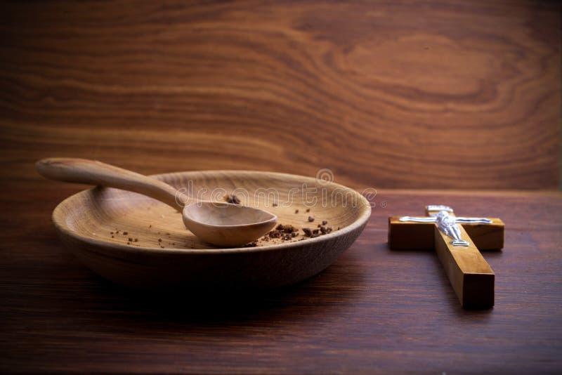 Νηστεία, που παραχωρεί Πιάτο και σταυρός στο ξύλινο backgroud στοκ εικόνες