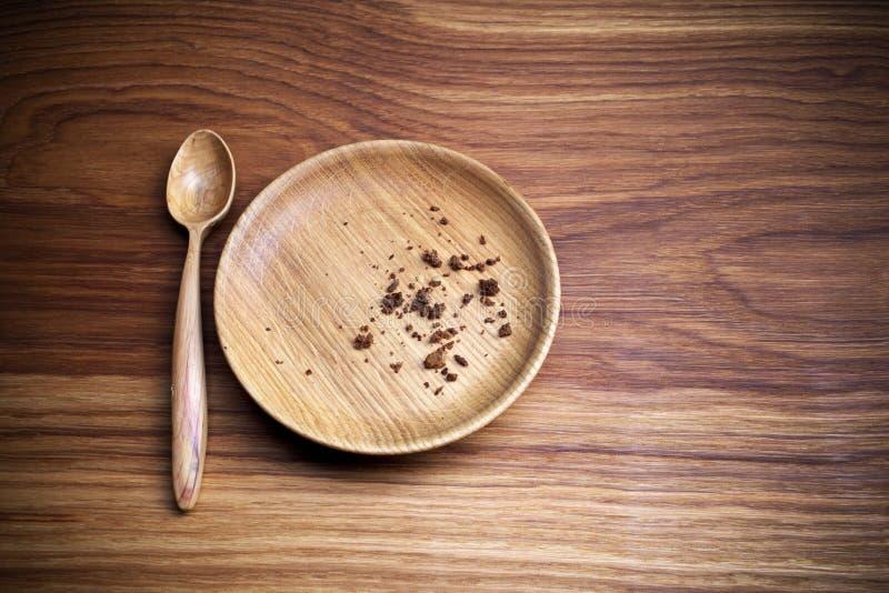 Νηστεία, που παραχωρεί Πιάτο με το κουτάλι και ψίχουλο στο ξύλινο υπόβαθρο στοκ εικόνες
