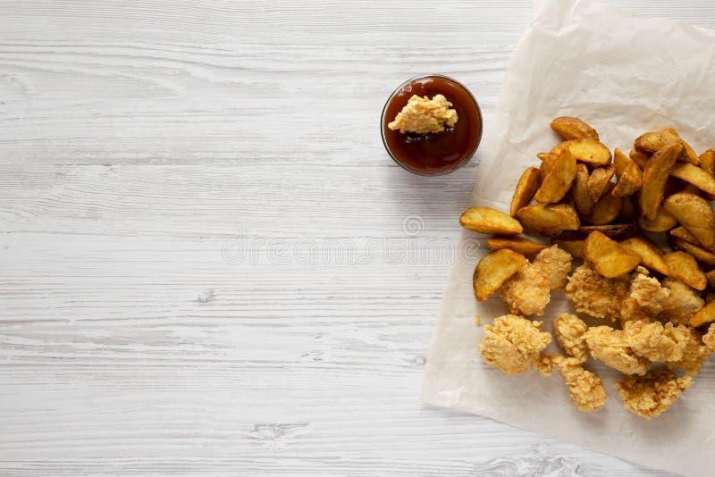 Νόστιμο γρήγορο γεύμα: τηγανισμένες σφήνες πατατών, δαγκώματα κοτόπουλου, bbq σάλτσα σε μια άσπρη ξύλινη επιφάνεια, τοπ άποψη Επί στοκ φωτογραφία με δικαίωμα ελεύθερης χρήσης