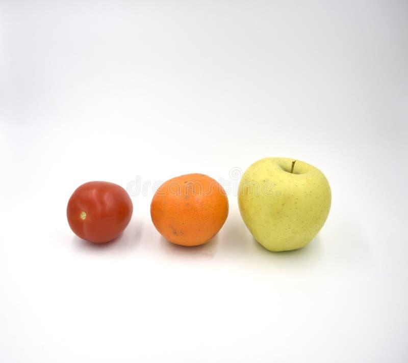 Ντομάτα, πορτοκάλι, μήλο στο άσπρο υπόβαθρο στοκ φωτογραφίες