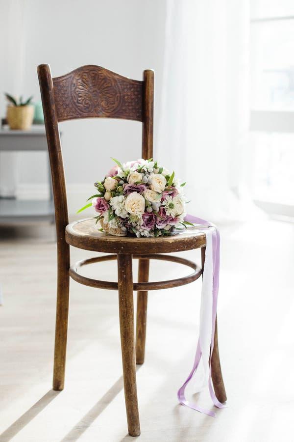 νυφικά χέρια νεόνυμφων νυφών ανθοδεσμών Όμορφος των άσπρων λουλουδιών και της πρασινάδας, στην εκλεκτής ποιότητας ξύλινη καρέκλα στοκ εικόνα με δικαίωμα ελεύθερης χρήσης