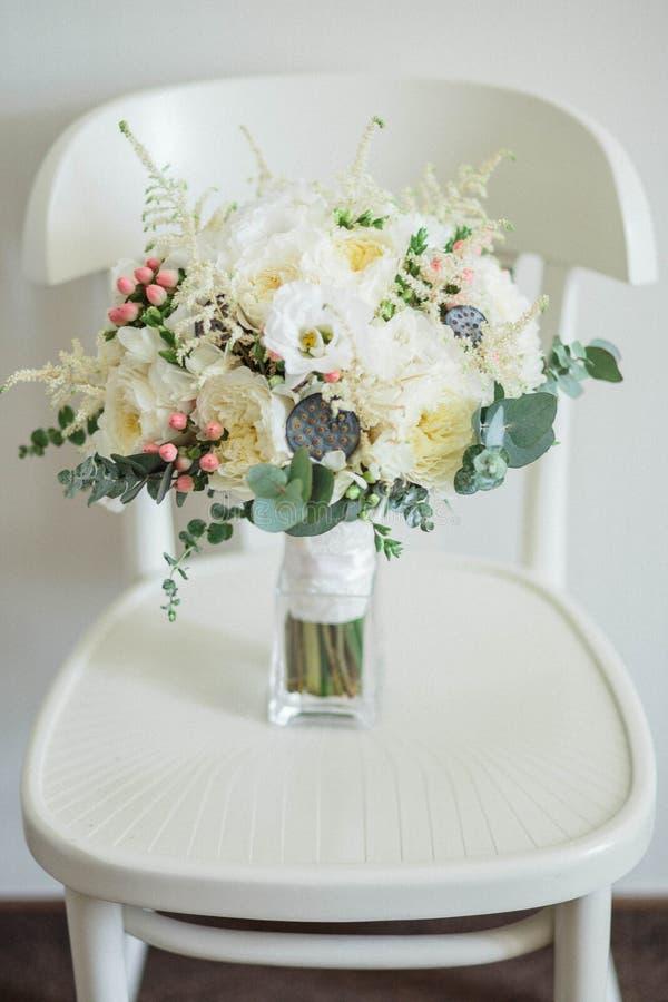 νυφικά χέρια νεόνυμφων νυφών ανθοδεσμών Όμορφος των άσπρων λουλουδιών και της πρασινάδας, στην εκλεκτής ποιότητας ξύλινη καρέκλα στοκ εικόνες