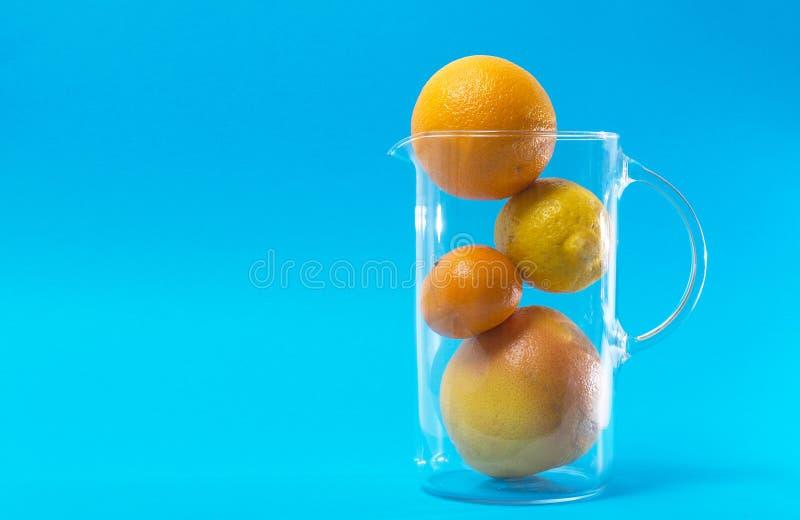 νωποί καρποί εσπεριδοε&iota Λεμόνι, μανταρίνι, γκρέιπφρουτ και πορτοκάλι Φρούτα στα γυαλικά στο μπλε υπόβαθρο στοκ εικόνες