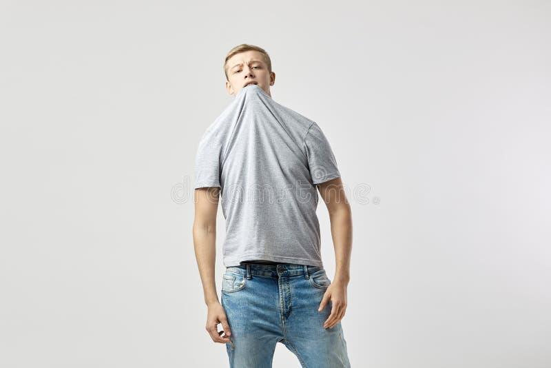 Ξανθός τύπος που ντύνεται σε μια άσπρη μπλούζα και τις στάσεις τζιν στο άσπρο υπόβαθρο στο στούντιο με την μπλούζα του σε δικοί τ στοκ φωτογραφία