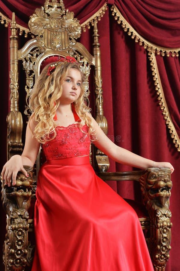 Ξανθό έφηβη στη φωτεινή κόκκινη συνεδρίαση φορεμάτων στην εκλεκτής ποιότητας καρέκλα στοκ εικόνα με δικαίωμα ελεύθερης χρήσης