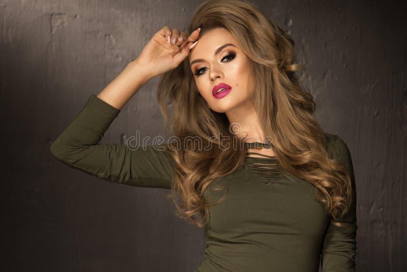 Ξανθό κορίτσι μόδας με τη μακριά και λαμπρή σγουρή τρίχα στοκ φωτογραφία