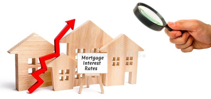 Ξύλινο σπίτι και τα ποσοστά τόκου στεγαστικών δανείων επιγραφής και επάνω στο βέλος Αύξηση των ποσοστών και του φόρου υποθηκών Η  στοκ φωτογραφία