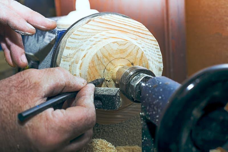 Ξυλουργός που εργάζεται σε έναν τόρνο στο ξύλο Ένα ανθρώπινο χέρι με ένα μολύβι επισύρει την προσοχή τα σημάδια στο προϊόν στοκ εικόνα